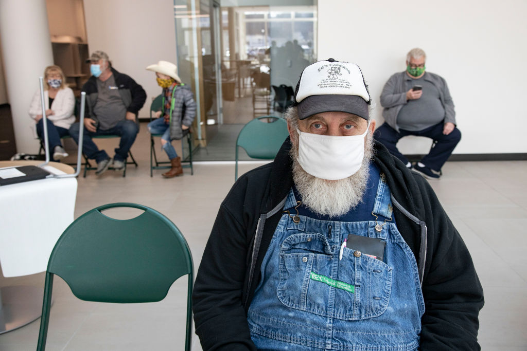 Edward Vires, 64, waits for a half hour after receiving the...