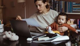 Female professional reading document while sitting with male toddler at home