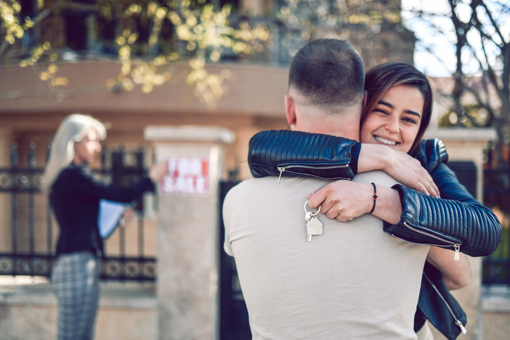 Happy Female Embracing Male While Buying New House From Real Estate Agent
