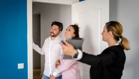 Real estate agent showing a property to a happy family