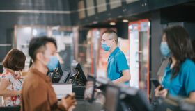 asian chinese customer with facemask buying movie tickets from cinema movie theater ticket counter