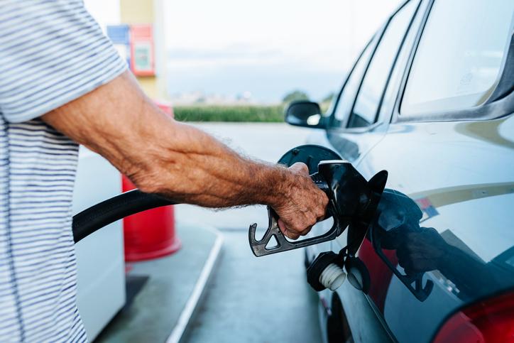 Senior man filling the tank of his car at the gas station.