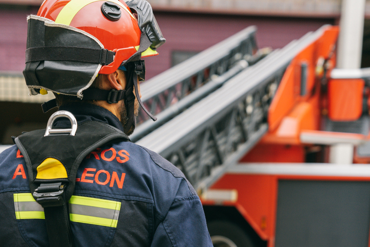 Back view of fireman wearing safety helmet and protective uniform standing near fire engine with ladder